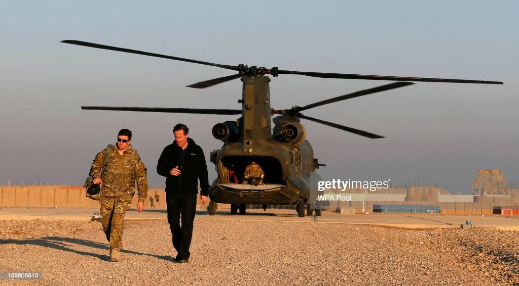 British Prime Minister David Cameron (R) arrives during a visit to Forward Operating Base Price on December 20, 2012 in Helmand Province, Afghanistan. Prime Minister Cameron is making a Christmas visit to British troops in the region amid tight security.