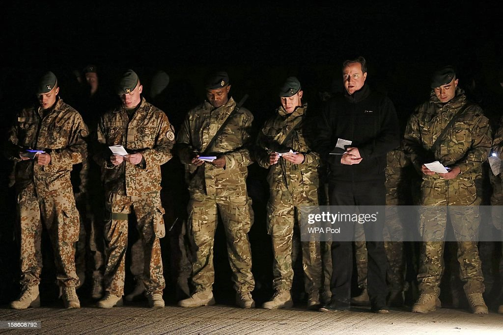 British Prime Minister David Cameron (2nd R) attends a carol service with British, Danish and Bosnian soldiers on December 20, 2012 in Helmand Province, Afghanistan. Prime Minister Cameron is making a Christmas visit to British troops in the region amid tight security.