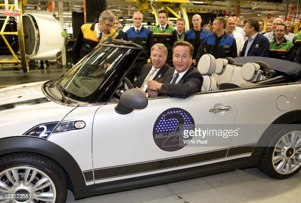 British Prime Minister David Cameron beside BMW group management member for production FrankPeter Arndt drives the two millionth MINI off the...