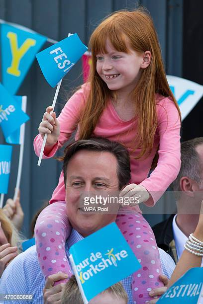 British Prime Minister David Cameron carries 7 year old Amelie Bone on his shoulders as he watches the Tour de Yorkshire cycle race pass through...