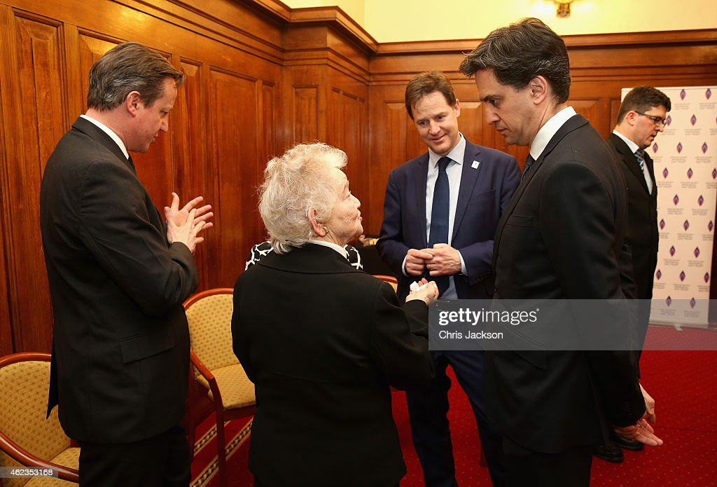 British Prime Minister David Cameron chats to a Holocaust survivor (obscured) as British Deputy Prime Minister Nick Clegg and Leader of the Labour Party, Ed Miliband talk to Holocaust survivor Anne Kirk at a Holocaust Memorial Day ceremony at Central Hall Westminster on January 27, 2015 in London, England.