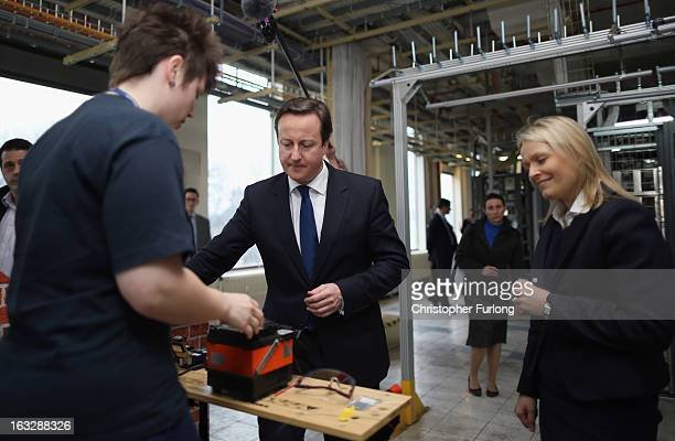 British Prime Minister David Cameron chats to Openreach apprentices as he tours a telephone exchange accompanied by Chief Executive of Openreach Liv...