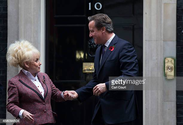 British Prime Minister David Cameron chats with actress Barbara Windsor as members of the armed forces and British Legion staff arrive from the poppy...