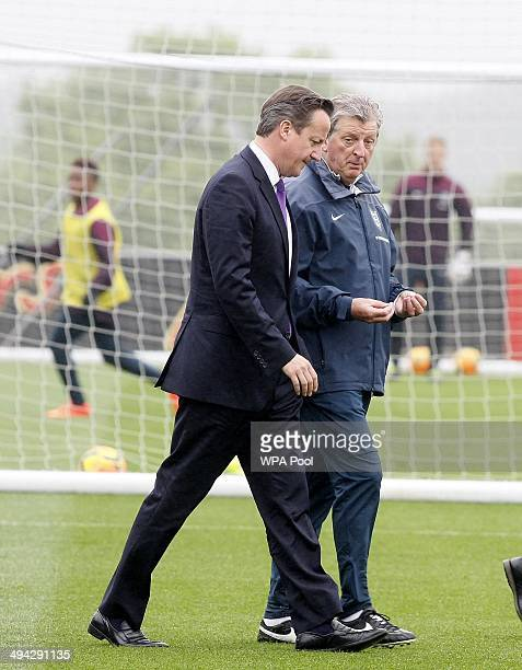 British Prime Minister David Cameron chats with England football manager Roy Hodgson during his visit to England's football training headquaters at...