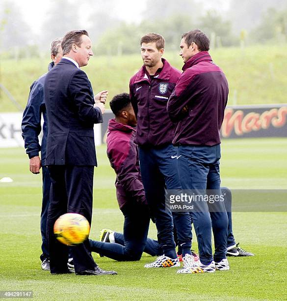 British Prime Minister David Cameron chats with England footballers Steven Gerrard and Frank Lampard during his visit to England's football training...