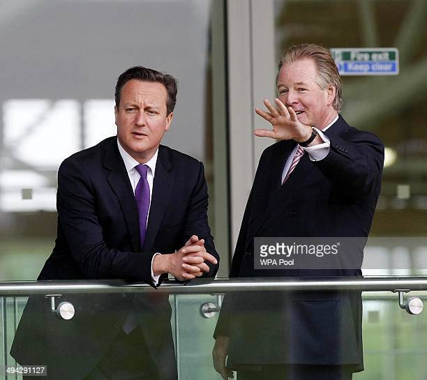 British Prime Minister David Cameron chats with the chairman of UK Community Foundations David Sheepshanks during his visit to England's football...
