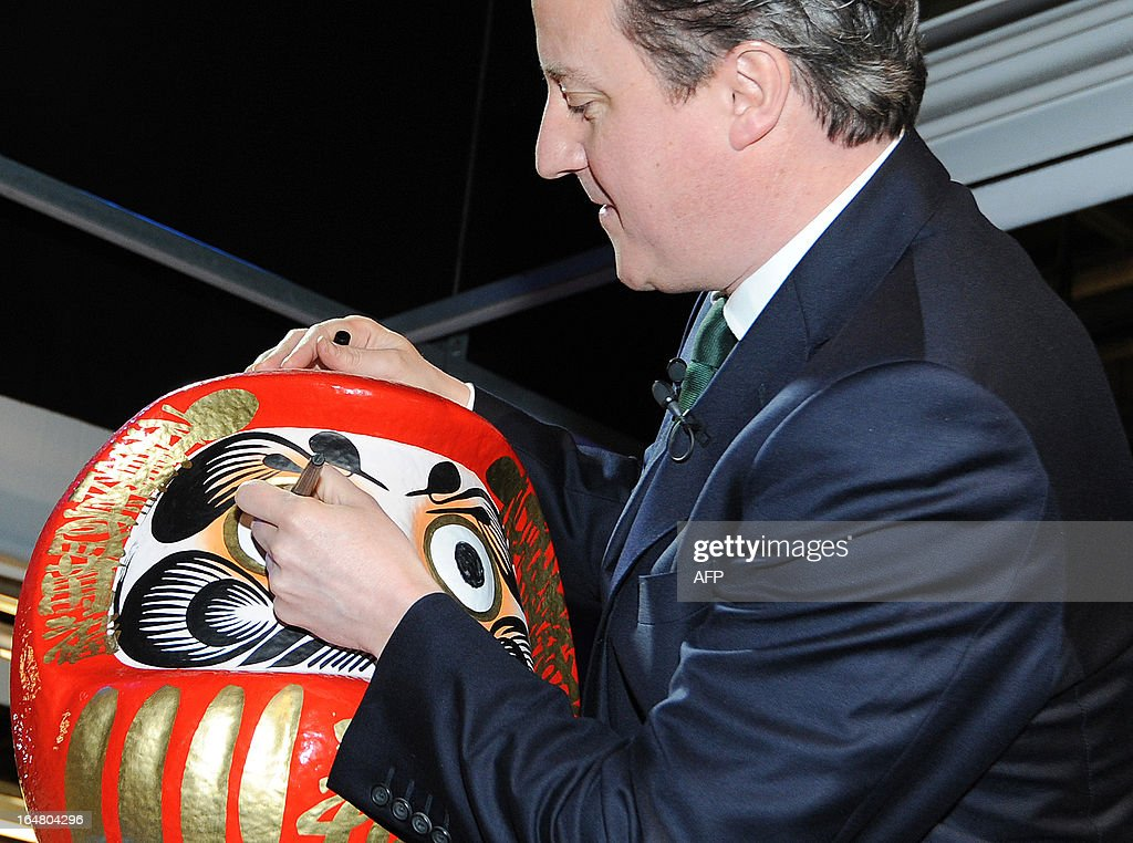 British Prime Minister David Cameron colours in the eye of a Daruma doll, a Japanese tradition symbolising the completion of a goal or project, during a visit to the Nissan factory in Sunderland, northeast England on March 28, 2013. Cameron visited the Sunderland manufacturing plant of Japanese auto-maker Nissan in Sunderland on March 28 as it was announced that the factor will start production of the Leaf electric vehicle.