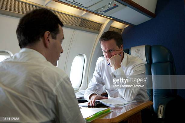 British Prime Minister David Cameron deep in thought over Europe as he listens to Chancellor George Osborne during an RAF flight taking them to...