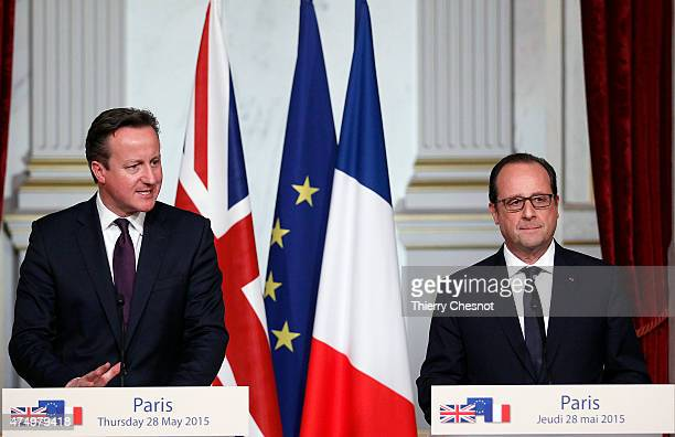 British Prime Minister David Cameron delivers a speech with French President Francois Hollande during a press conference after their meeting at the...