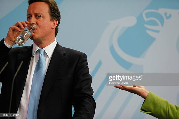 British Prime Minister David Cameron drinks water during a press conference when German Chancellor Angela Merkel gestures to him after their meeting...
