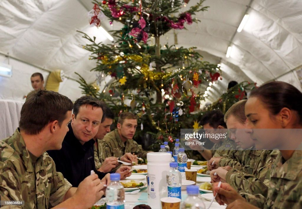 British Prime Minister David Cameron (2nd L) eats dinner with British soldiers during a visit to Forward Operating Base Price on December 20, 2012 in Helmand Province, Afghanistan. Prime Minister Cameron is making a Christmas visit to British troops in the region amid tight security.
