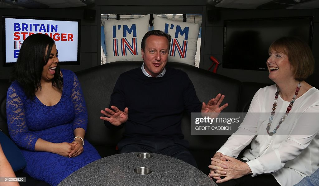 TOPSHOT - British Prime Minister David Cameron (C) gestures as he talks with Founder of Isabella Queen bags, Isabelle Ugochukwu (L), and Labour's Harriet Harman, as he travels on his campaign bus from Bristol, south-west England, on June 22, 2016, as the prime minister campaigns to avoid a Brexit ahead of the June 23 EU referendum. Rival sides threw their efforts into the final day of campaigning Wednesday, on the eve of Britain's vote on EU membership that will shape the future of Europe. / AFP / POOL / Geoff CADDICK