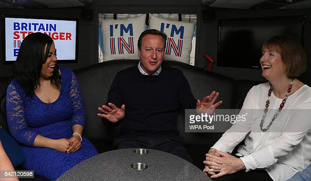 British Prime Minister David Cameron gestures as he talks with Founder of Isabella Queen bags Isabelle Ugochukwu and Labour MP Harriet Harman as he...