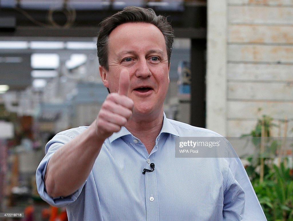 British Prime Minister David Cameron gestures to supporters during an election rally at Squires garden centre on May 5, 2015 in Twickenham, London. Britain will go to the polls in a national election in just two days time.