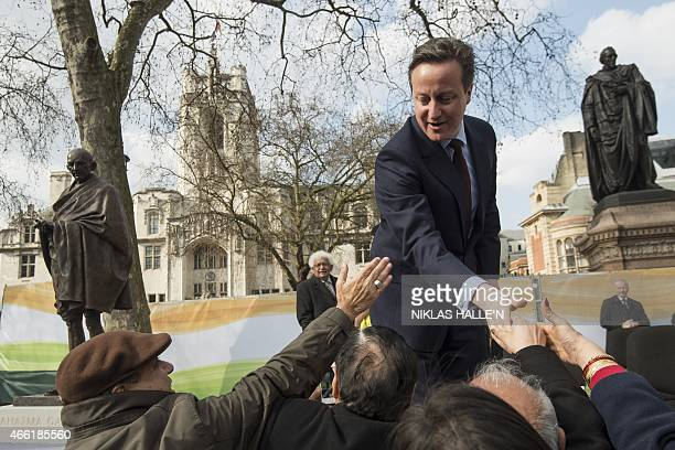 British Prime Minister David Cameron greets a crowd during a ceremony unveiling a statue of Mahatma Gandhi in Parliament square in central London on...