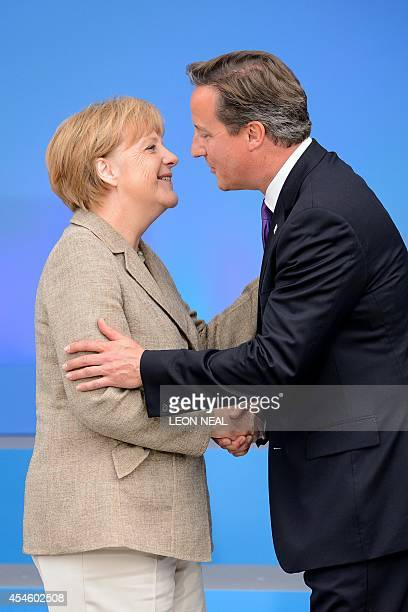British Prime Minister David Cameron greets German Chancellor Angela Merkel during the 2014 NATO Summit in Newport Wales on September 4 2014 NATO...
