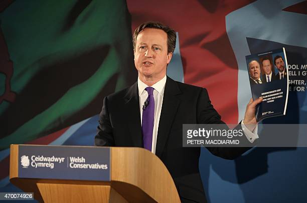 British Prime Minister David Cameron holds up a copy of the Conservative Welsh manifesto as he speaks to supporters on April 17 2015 in Builth Wells...