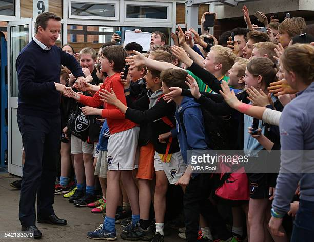 British Prime Minister David Cameron is greeted by children as he arrives to visit The Warriner School a secondary school in Bloxham near Banbury on...