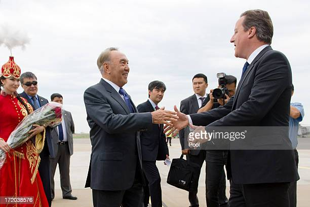 British Prime Minister David Cameron is greeted by Kazakhstan President Nursultan Nazarbayev after landing at Atyrau airport on July 1 2013 in Atyrau...