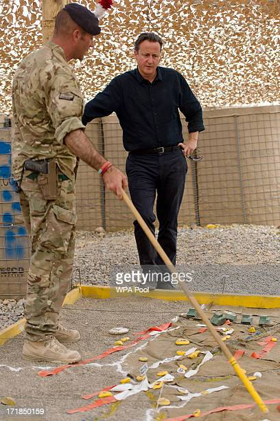 British Prime Minister David Cameron is shown a map of the area by Major Jim Skelton during a visit to Camp Bastion on June 29 2013 near Lashkar Gah...