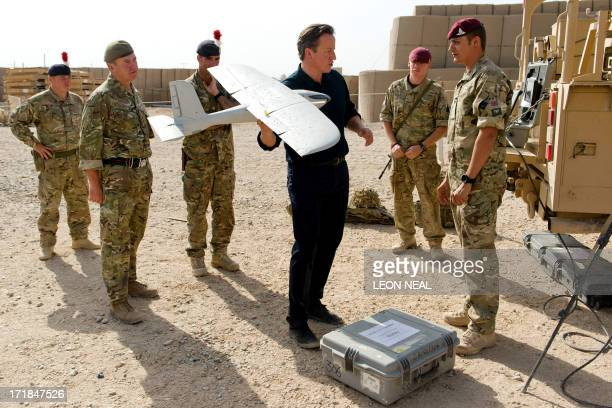 British Prime Minister David Cameron is shown a remotecontrolled surveillance aircaft used in regional operations during a visit to Camp Bastion in...