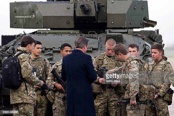 British Prime Minister David Cameron is shown the rifle of a Royal Welsh Infantry soldier as they stand in front of a Lockheed Martin Warrior...