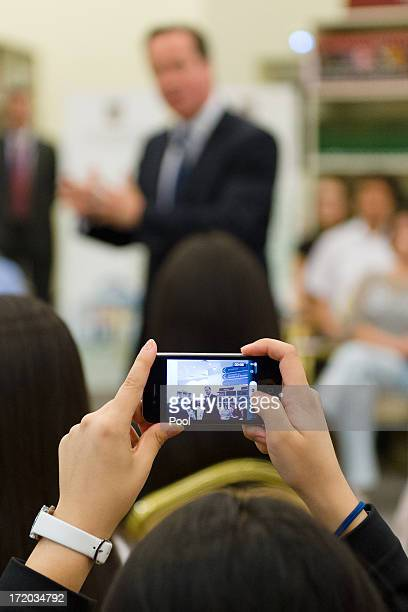British Prime Minister David Cameron is viewed through a smartphone camera as he addresses students during a PM Direct event at Nazarbayev University...