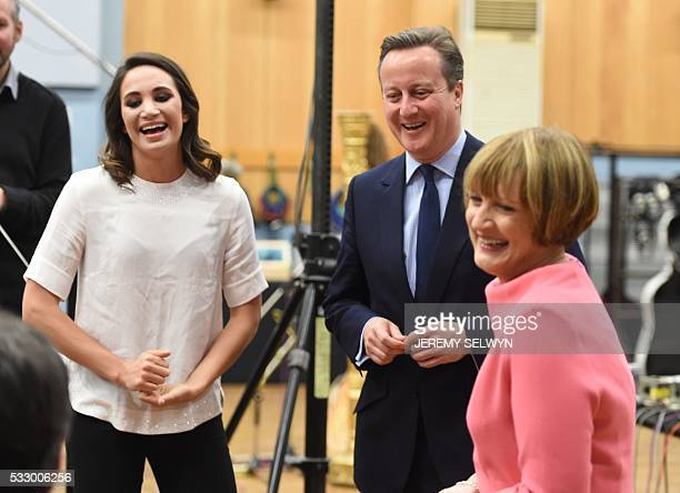 British Prime Minister David Cameron laughs with British Labour Party politician Tessa Jowell and British singer Laura Wright while on a visit to...