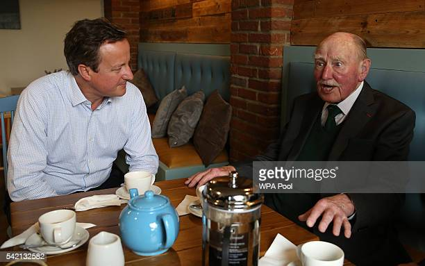 British Prime Minister David Cameron listens as he meets with former British Royal Marine Commando andD Day veteran Patrick Churchill at the Millets...
