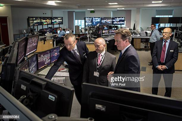 British Prime Minister David Cameron looks at signalling computer monitors in the signal room at Network Rail Operating Centre on November 21 in...