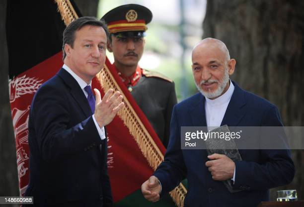 British Prime Minister David Cameron meets with Afghan President Hamid Karzai during a press conference before arriving at the Presidential Palace on...