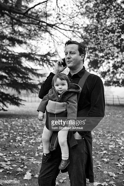 British Prime Minister David Cameron pauses to take a phone call from his Downing Street office during a Saturday morning walk with baby daughter...