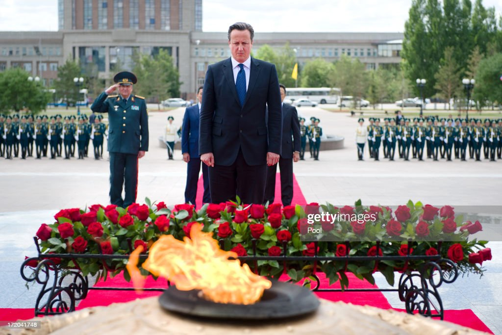 British Prime Minister David Cameron (C) pays his respects after laying a wreath at the Monument of the Motherland Defenders on July 1, 2013 in Astana, Kazakhstan. Cameron is visiting Kazakhstan as part of a trade mission; the first ever trip to the country by a serving British Prime Minister, after making an unannounced trip to visit troops in Afghanistan and meeting with the Prime Minister of Pakistan in Islamabad.