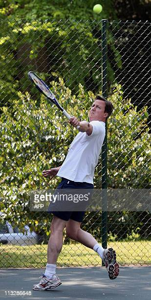British Prime Minister David Cameron plays a shot during a charity tennis match with former Wimbledon tennis champion Boris Becker at Chequers the...