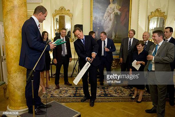 British Prime Minister David Cameron plays a shot with a cricket bat he was presented with by director of cricket for the England and Wales Cricket...