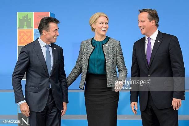 British Prime Minister David Cameron poses for pictures with NATO Secretary General Anders Fogh Rasmussen and Danish Prime Minister HelleThorning...