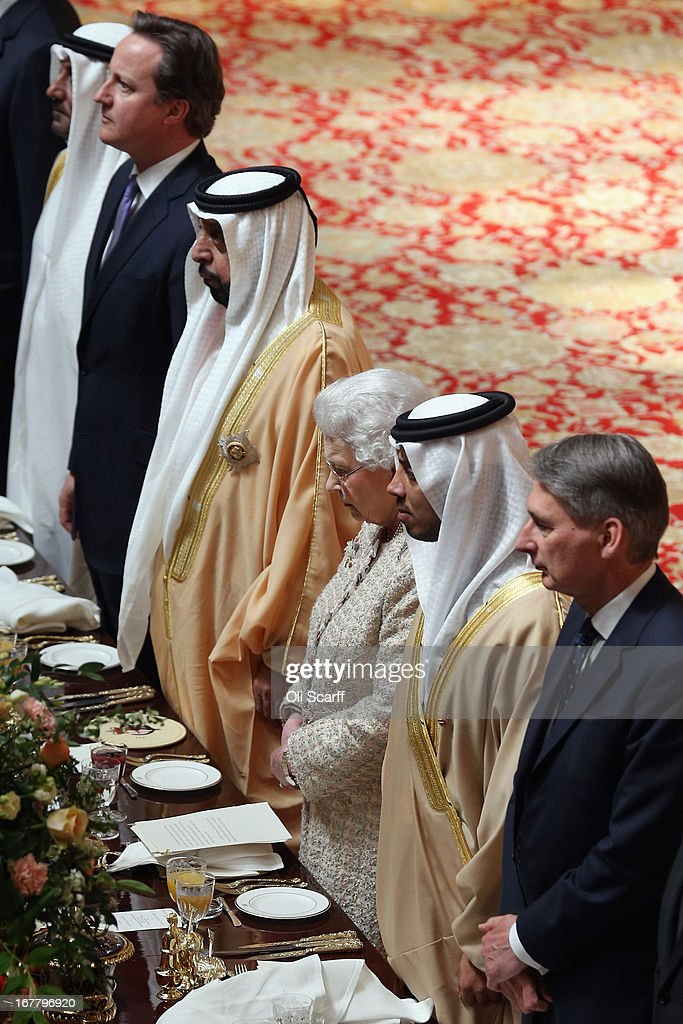 British Prime Minister David Cameron (2nd L), Queen Elizabeth II (C) British Defence Secretary Philip Hammond (R) and The President of the United Arab Emirates, His Highness Sheikh Khalifa bin Zayed Al Nahyan (3rd L), listen to the national anthem at a State Luncheon for His Highness Sheikh Khalifa in Windsor Castle on April 30, 2013 in Windsor, England. The President of the United Arab Emirates is paying a two-day State Visit to the United Kingdom, staying in Windsor Castle as the guest of Her Majesty The Queen from April 30, 2013 to May 1, 2013. Sheikh Khalifa will meet the British Prime Minister David Cameron tomorrow at his Downing Street residence.