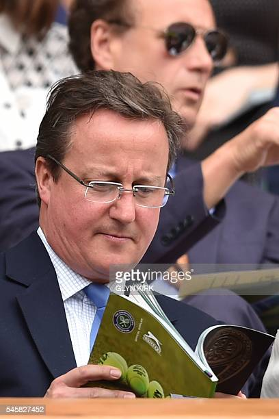 British Prime Minister David Cameron reads a programme in the royal box on centre court before the men's singles final match on the last day of the...