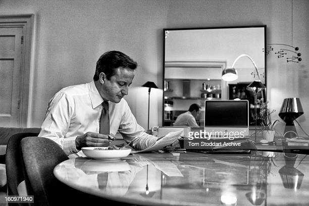 British Prime Minister David Cameron reads government papers while having a sandwich lunch in the flat above 11 Downing Street where he and his...