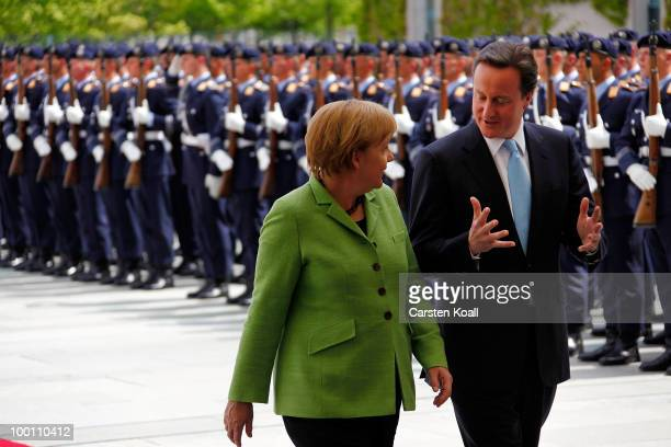 British Prime Minister David Cameron reviews the guard of honor with German Chancellor Angela Merkel during his welcoming ceremony at the Chancellery...