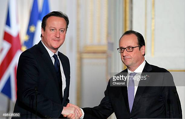 British Prime Minister David Cameron shakes hand with French President Francois Hollande after a press conference at the Elysee Palace on November 23...