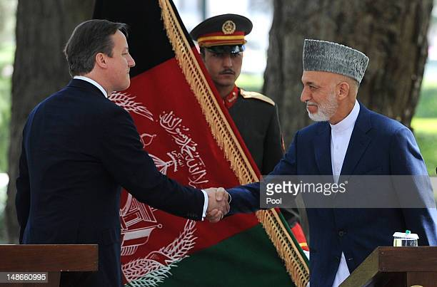 British Prime Minister David Cameron shakes hands with Afghan President Hamid Karzai during a press conference before arriving at the Presidential...