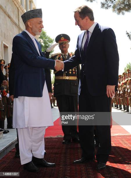 British Prime Minister David Cameron shakes hands with Afghan President Hamid Karzai before arriving at the Presidential Palace on July 19 2012 in...
