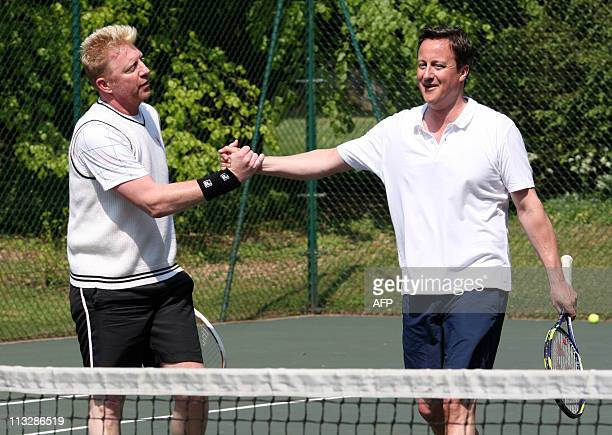 British Prime Minister David Cameron shakes hands with former Wimbledon tennis champion Boris Becker after a charity match at Chequers, the Prime...