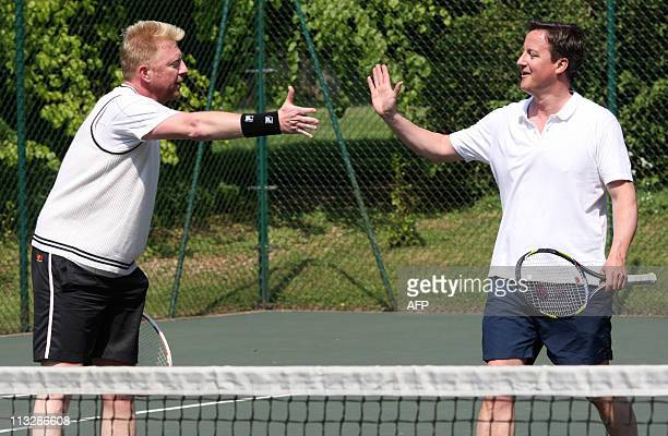 British Prime Minister David Cameron shakes hands with former Wimbledon tennis champion Boris Becker after a charity match at Chequers the Prime...
