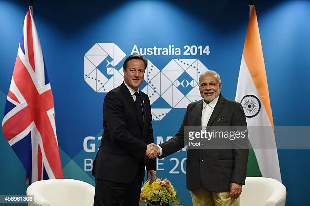 British Prime minister David Cameron shakes hands with Indian Prime Minister Narendra Modi during a bilateral meeting at the Brisbane Convention and...
