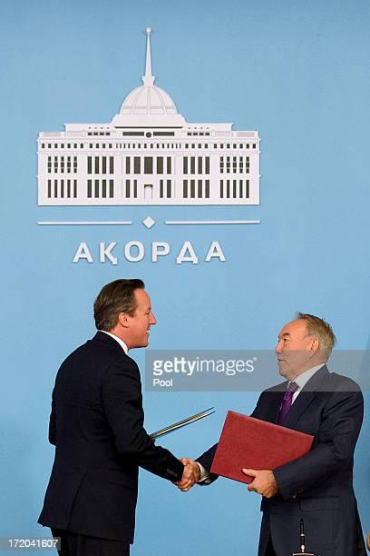 British Prime Minister David Cameron shakes hands with Kazakhstan President Nursultan Nazarbayev after signing a strategic partnership agreement at...
