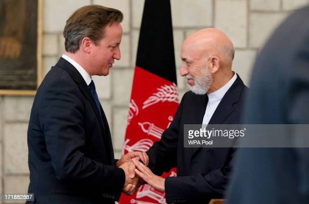 British Prime Minister David Cameron shakes hands with President of Afghanistan Hamid Karzai following a press conference in the Presidential Palace...