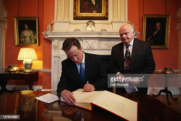 British Prime Minister David Cameron signs a Book of Commitment pledging his support and commitment to remembering the Holocaust at 10 Downing Street...