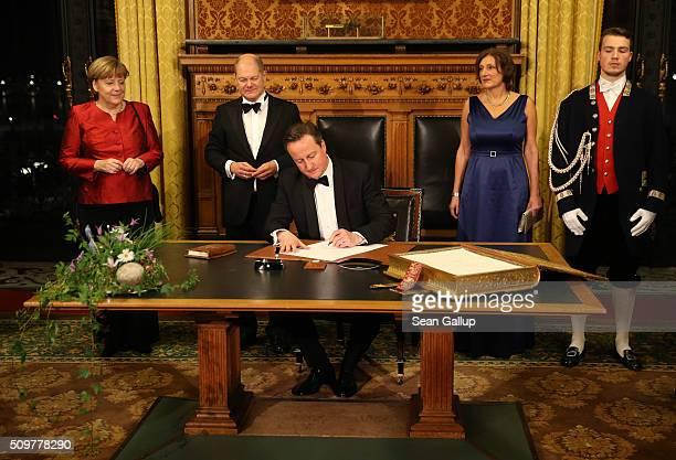 British Prime Minister David Cameron signs the Golden Book of Hamburg as German Chancellor Angela Merkel Hamburg's Mayor Olaf Scholz and his wife...